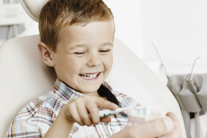 A small child being shown how to brush his teeth